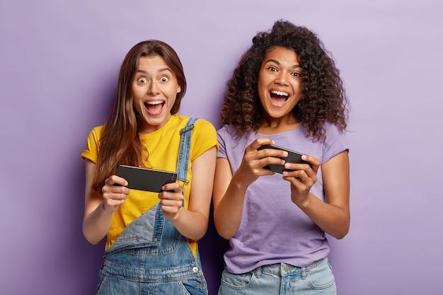 Dolle vrouwelijke bloggers van gemengd ras lachen en communiceren met volgers op mobiele telefoons