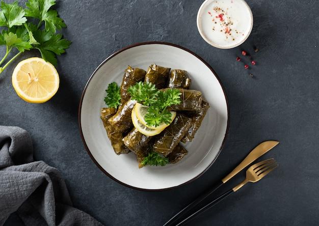 Dolma - gevulde druivenbladeren met rijst en vlees op een donkere achtergrond, weergave van bovenaf. traditioneel grieks. kaukasische en turkse keuken