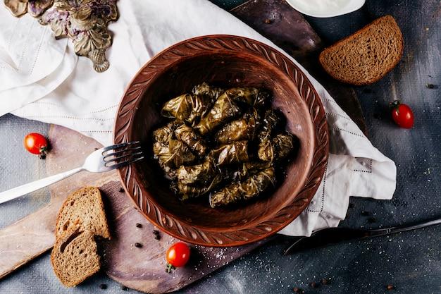 Dolma groen een bovenaanzicht binnen bruine plaat rond rode kerstomaatjes en brood slcies op het donkere oppervlak