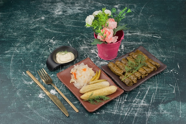 Dolma met zure room en bord zoute kool en komkommer met emmer met onderpompen.