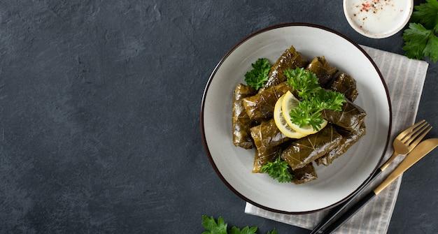 Dolma op een donkere achtergrond. traditionele kaukasische, turkse en griekse keuken, bovenaanzicht, plaats voor tekst