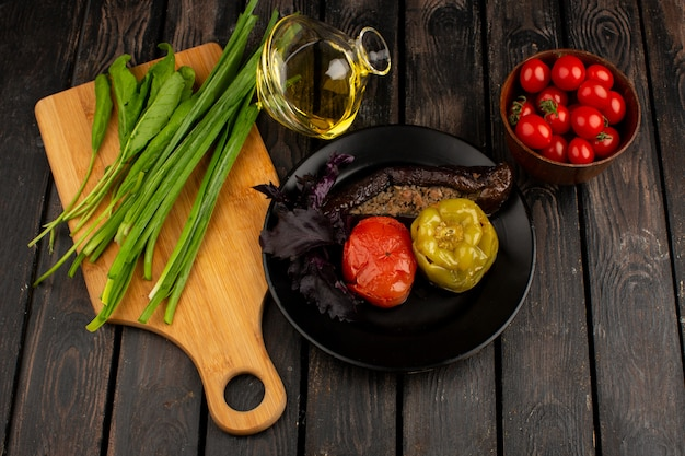 Dolma plantaardige dolma met gehakt binnen met groene olijfolie en rode tomaten op het rustieke houten bureau