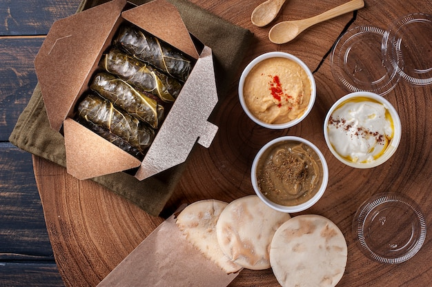 Dolma, sarma of turkse dolmades. traditionele mediterrane schotel dolmadakia of tolma. gevulde druivenbladeren. verpakking voor levering