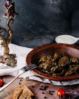 Dolma smakelijke gezouten vleesmaaltijd binnen bruine plaat op de donkere oppervlakte