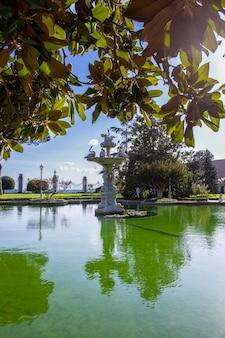 Dolmabahce palace tuinen met veel groen, fontein en vijver met water in istanbul, turkije