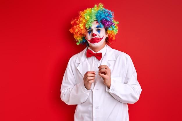Dolorous clown met geschilderde kleurrijke make-up gezicht, boos harlekijn geïsoleerd op rode studio achtergrond