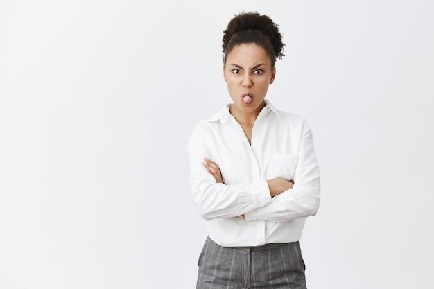 Dom en kinderachtig schattig afro-amerikaanse vrouw in wit overhemd met tong, beledigd op zoek