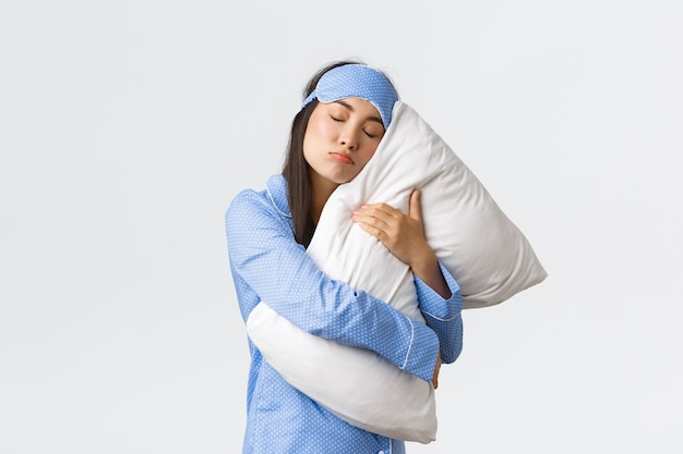 Dom en schattig aziatisch meisje in blauw slaapmasker en pyjama, kussen strak knuffelen als onwillig wakker worden, wil niet opstaan uit bed in de ochtend, zware slaper poseren op witte achtergrond.