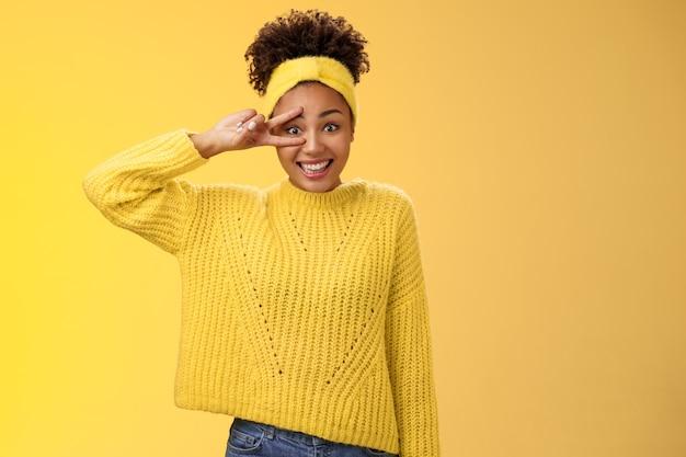Dom onzeker schattig onhandig jong millennial meisje blozend onzeker fotograferen glimlachen toon vredesoverwinningsteken in de buurt van oog slecht in poseren, staande vriendelijke gele achtergrond. ruimte kopiëren