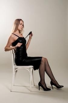 Dominante vrouw in een leren jurk met een pak slaag in de hand.