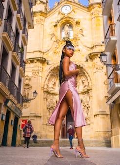 Dominicaanse etnische meisje met vlechten met een mooie roze jurk. mode genieten van de zomer in een prachtige kerk van de stad, verleidelijke look