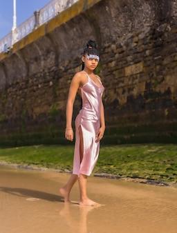 Dominicaanse etnische meisje met vlechten met een mooie roze jurk. mode genieten van de zomer wandelen op het strand