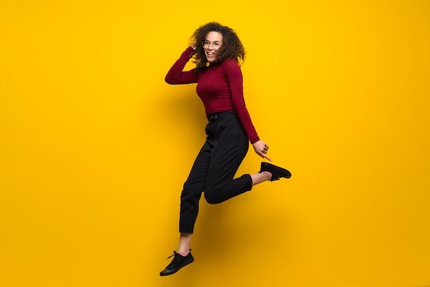 Dominicaanse vrouw die met krullend haar over geïsoleerde gele muur springt