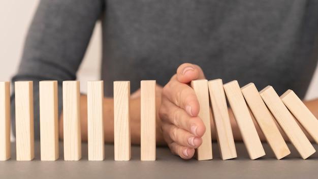 Domino gemaakt met houten stukken die financiële problemen vertegenwoordigen
