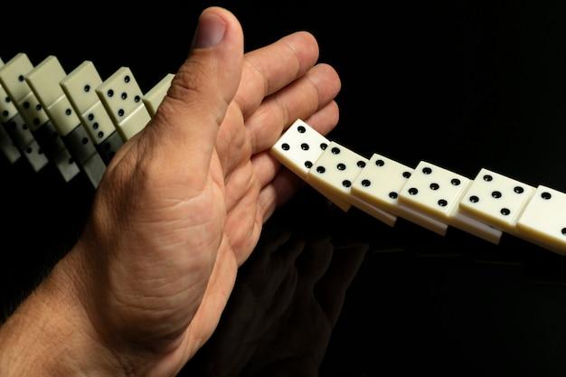 Domino-knokkels die achter elkaar vallen, worden met de hand gestopt op een zwarte glazen tafel