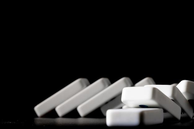 Domino's die zich op een rij op zwarte achtergrond bevinden