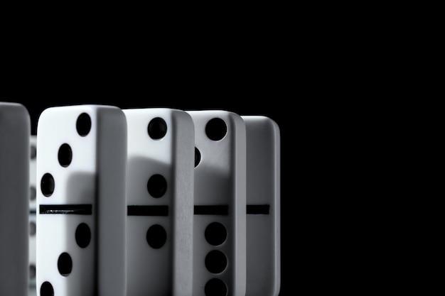 Domino's die zich op een rij op zwarte muur bevinden