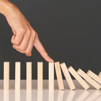 Domino-spel gemaakt met houten stukken die financiële problemen voorstellen