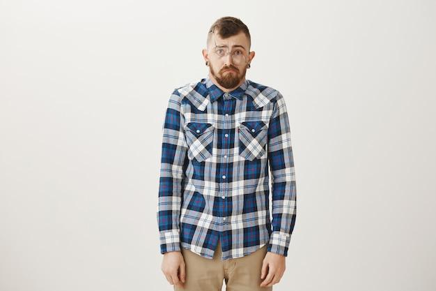 Domme, droevige en onhandige man met een kromme bril die eruitziet als een loser