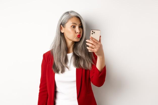 Domme en grappige aziatische senior vrouw steenbolk, selfie nemen op smartphone, staande op witte achtergrond.