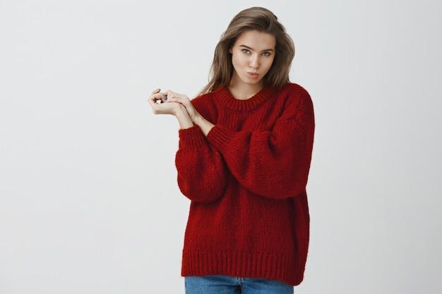 Domme en speelse sexy vrouw in rode losse warme trui die flirterige blikken maakt die lippen vouwen die lucht sturen mwah met handpalmen tegen elkaar gedrukt, schattig, verleidelijk met blikken over witte muur