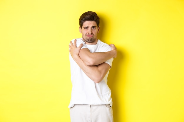 Domme en timide man die zichzelf probeert te troosten, zijn lichaam knuffelt en fronsend bang, staande over een gele achtergrond.