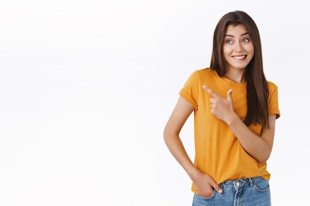 Domme flirterige vrouw houdt een beetje van kleding in de winkel, bijt op lip en glimlacht, kijkt gefascineerd en geïnteresseerd, wijst naar links, verlangend gezicht, vraagt vriendin om te kopen met onschuldige uitdrukking