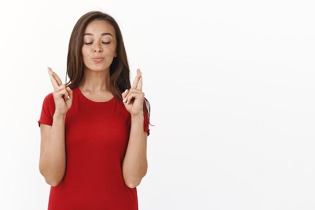 Domme hoopvolle glamourvrouw in rood t-shirt, sluit ogen trouw kruis vingers veel geluk, pruilend van verwachting en vreugde, biddend voor een droom die uitkomt, smekend wens vervullen, witte muur