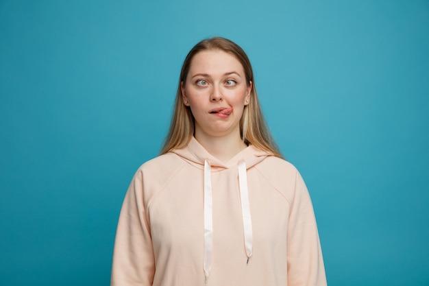 Domme jonge blonde vrouw die tong met gekruiste ogen toont