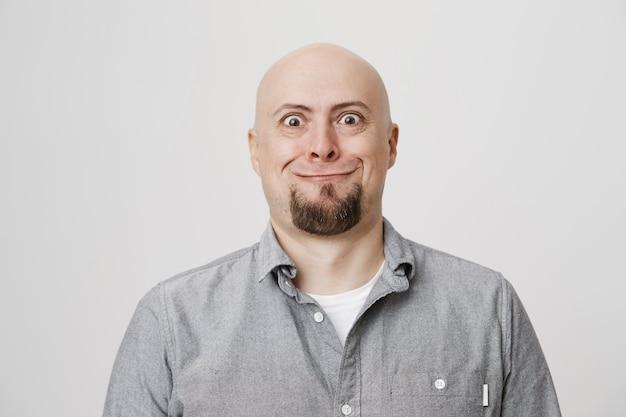Domme kale man van middelbare leeftijd met baard die enge glimlach trekt