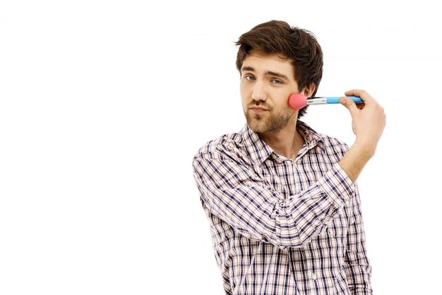 Domme man brengt blush make-up aan met borstel
