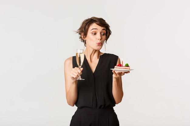 Domme mooie meid viert haar verjaardag, houdt een glas champagne vast en doet een wens op een verjaardagstaart, staande over wit.