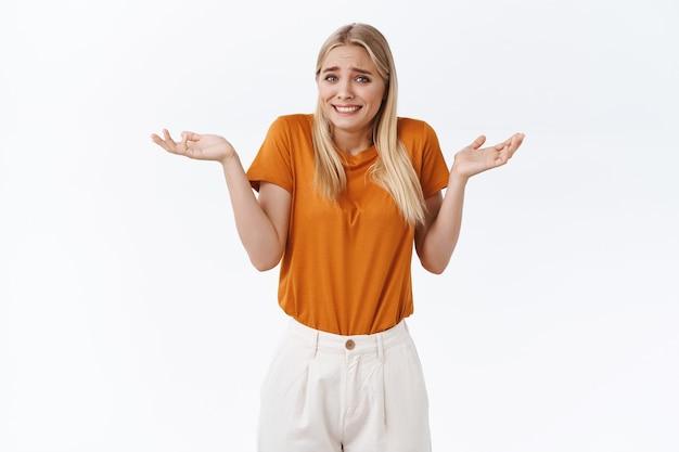 Domme onvoorzichtige, gemakkelijke moderne aantrekkelijke blonde vrouw in oranje t-shirt, broek, handen opzij in de buurt van schouders, schouderophalend en ongehinderd glimlachen, onvoorzichtig en onbewust staan