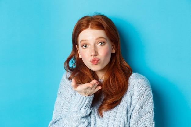 Domme roodharige vrouw in trui, blaast luchtkus naar de camera met gebobbelde lippen, staande tegen een blauwe achtergrond