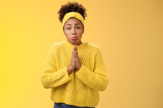 Domme schattige pitty jonge afro-amerikaanse tienerdochter die zakgeld vraagt, ga trip, druk op palmen smeekbede bid hulp nodig, bedelen, maak droevige mokkende ellendige uitdrukking, staande gele achtergrond.