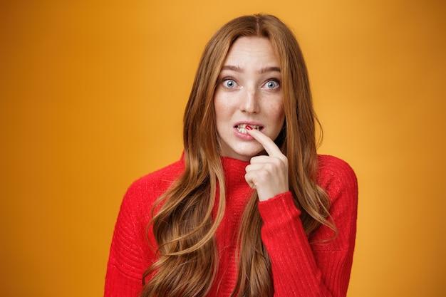 Domme, schattige roodharige vrouw die onschuldige oeps-uitdrukking maakt terwijl ze de vinger op de lip houdt en bang kijkt met een ondervraagde uitdrukking op de camera die een fout maakt en probeert weg te komen van problemen met een flirterige blik