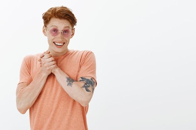 Domme vrolijke roodharige man in zonnebril die er blij uitziet, een geschenk of compliment krijgt