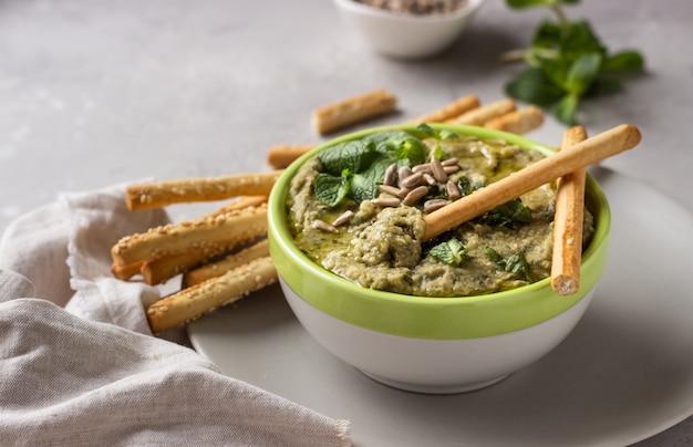 Dompel met mungbonen, munt en zaden geserveerd met grissini of gezouten broodstengels.