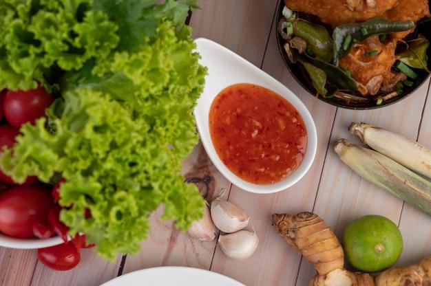 Dompelen, citroengras, knoflook, limoen, galangal, tomaat en salade op de houten vloer