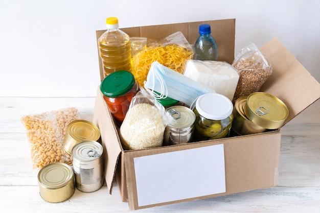 Donatie box met verschillende etenswaren. open kartonnen doos met olie, ingeblikt voedsel, granen en pasta.