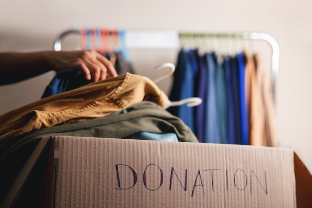 Donatie concept. gebruikte oude kleren van kledingrek in een donatiedoos klaarmaken