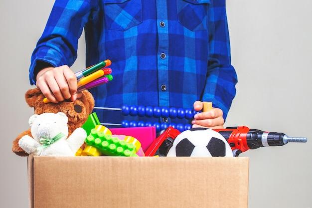 Donatie concept. kid bedrijf doneren doos met kleding, boeken, schoolbenodigdheden en speelgoed.