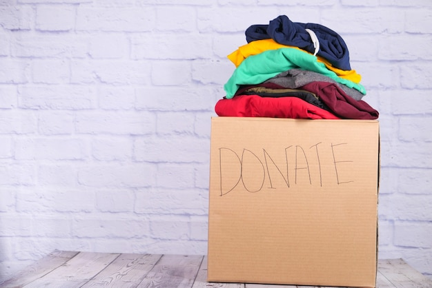 Donatiebox met donatiekleding op een houten achtergrond