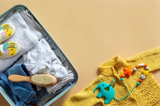 Donatiebox met neutrale babykleding, speelgoed en donatieaccessoires voor baby's op beige