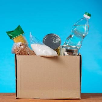 Donatiebox vol met verschillende producten op blauwe achtergrond. vierkant beeld