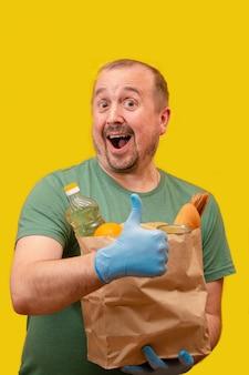 Donatieconcept: vrolijke lachende man met baard in groen t-shirt en blauwe medische handschoenen, houdt een duim omhoog en houdt met de andere hand donatiezak met voedsel vast