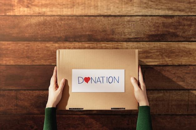 Donatieconcept. vrouw met doos met dingen met schenkingsetiket en hart. thuis voorbereiden op houten tafel. bovenaanzicht