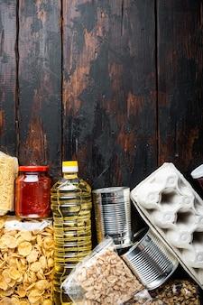 Donaties voedsel set van basisproducten en ingeblikte maaltijden, plat leggen, op houten tafel