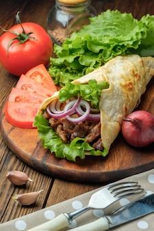 Doner kebab ligt op de snijplank. shoarma met vlees, uien, salade ligt op een witte oude houten tafel.