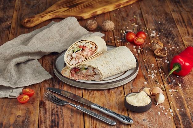 Döner kebab (shoarma of döner wrap). gegrilde kip op lavash met tomaten, groene salade en paprika op de houten tafel